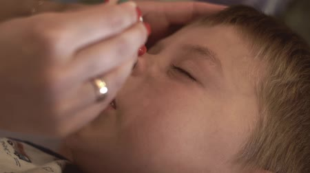 доза : Mom drips medical drops in nose sick child. Healthy care concept