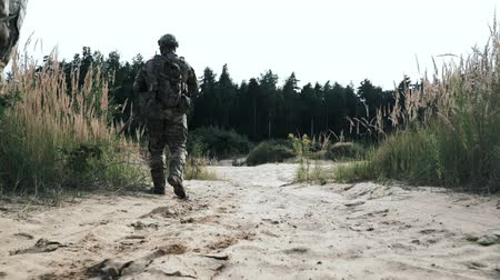 troop : Military soldiers with weapons walking on sand back view. Military mens