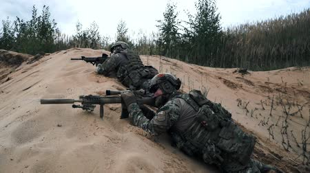 snajper : Military soldiers with sniper rifle lying in ambush on sand side view