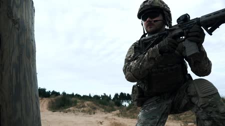 storming : Military soldier sitting on knee on sand and looking in optical sight