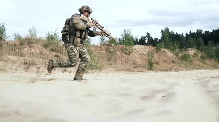 storming : Military soldier with sniper rifle running on sand side view. Military gear