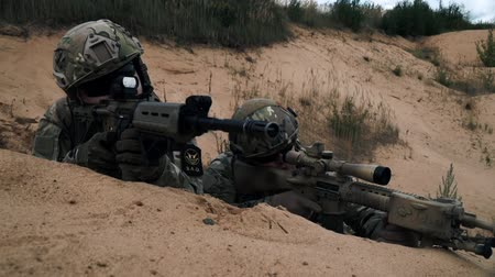 стрельба : Soldiers with sniper rifle lying on sand front view. Soldiers with weapons Стоковые видеозаписи