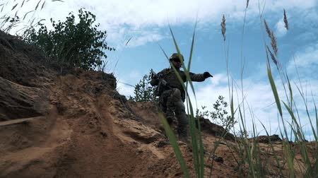 troop : Soldiers with military weapons jumping down from sand hill in quarry Stock Footage