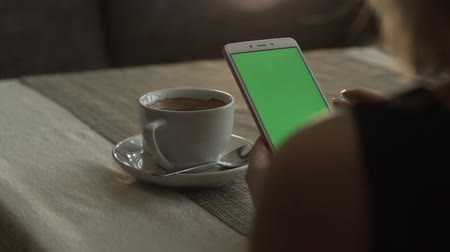 приложение : Woman hands touching on green screen mobile phone on background coffee cup