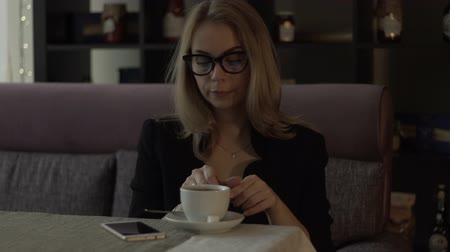 кафетерий : Young businesswoman in glasses drinking coffee from cup at table in modern cafe