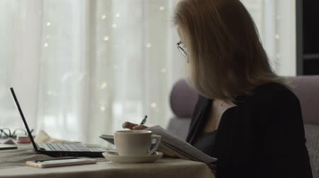 diary : Business woman typing on keyboard notebook and writing in diary in cafe Stock Footage