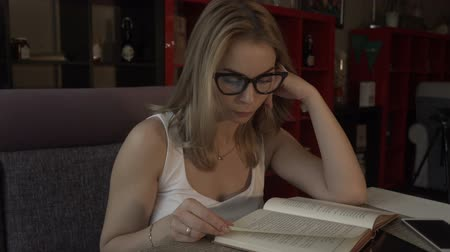 livro : Beautiful woman in glasses reading a book sitting at table on cozy couch in cafe Vídeos