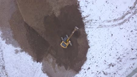 crawler : Drone view excavator working on industrial area on snowy ground
