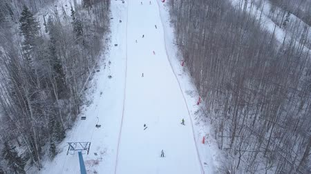 winda : People skiing and snowboarding on snowy slope past ski elevator in ski resort Wideo