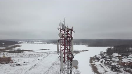 iletmek : Aerial view mobile tower with antennas dish for mobile wave in winter village. Drone view communication tower with satellite dishes for radio and television broadcast. Stok Video