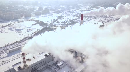 kotel : Aerial shooting from flying drone smoke clouds from industrial pipes on chemical plant in city. Smoking chimney on heting plant in modern city drone view. Smoke emission from boiler pipes.