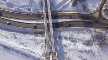 süspansiyon : Cars and cargo trucks moving on winter highway under train bridge drone view. Car traffic on snowy road on winter landscape. Aerial view suspension railway bridge over highway road. Stok Video