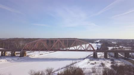 water rail : Suspension railway bridge for train traffic over frozen river on winter landscape aerial view. Car traffic on winter highway over train bridge drone view.