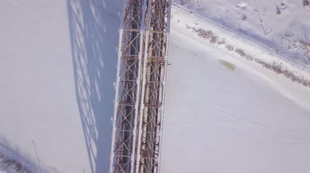 water rail : Railway bridge for train movement over frozen river on winter landscape drone view. Aerial view suspension train bridge through winter river.
