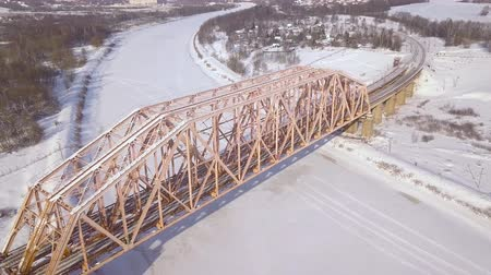 water rail : Railway bridge and railway track for train traffic over frozen river on winter landscape drone view. Suspension train bridge through river and car highway aerial view. Stock Footage