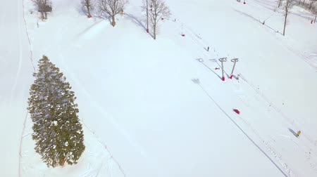chairlift : Winter activities skiing and snowboarding on snow slope aerial view. People on ski elevator in ski resort drone view. Winter vacation on luxury ski resort.