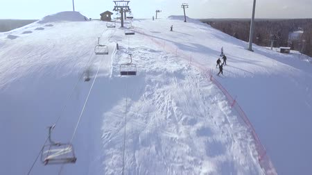 lodge : People skiing on snow slope on winter vacation at ski resort aerial view. Ski elevator fro skiing and snowboarding. Winter activity on snow mountain on drone view. Stock Footage