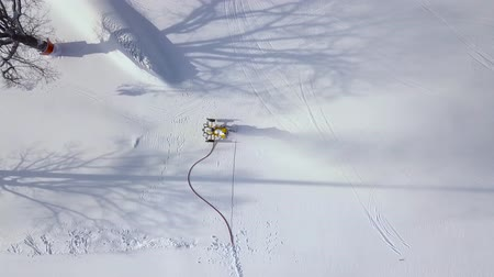 домик : Snow cannon in action on mountain at ski resort aerial view. Drone view snow cannon working on ski mountain.