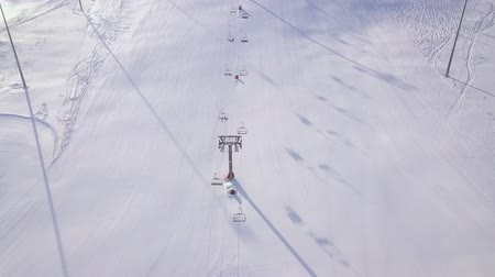 домик : People skiing and snowboarding on snow slope in winter ski resort. Ski elevator on snow mountain drone view. Winter activity on ski resort aerial view. Стоковые видеозаписи