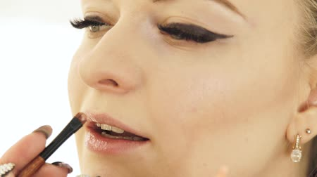 face painting : Hand makeup artist with cosmetic brush painting lips on woman face. Makeup lips close up