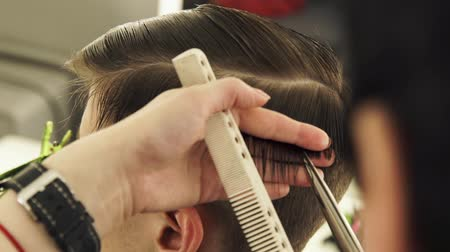 combing : Haircutter combing hair and cutting with hairdressing scissors in beauty school close up. Hairdresser doing male hairstyle with comb and hairdressing scissors in barber shop.