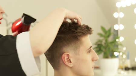 kurutma : Hairdresser drying and styling male hair after cutting in hairdressing salon. Close up barber styling hair with dryer after washing. Finish hairdressing in beauty studio. Stok Video