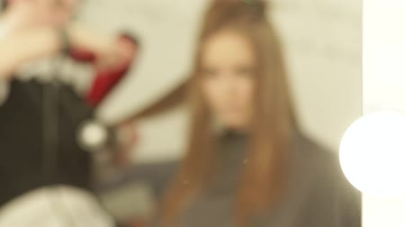 vágás : Blurred reflection in mirror hairdresser making woman hairstyling long hair with dryer and brush in beauty salon. Hairstyling fashion model in dressing room.