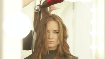 cutting up : Young woman during drying long hair with dryer and hairbrush front mirror in hairdressing salon. Close up hairstylist drying woman hair with dryer and comb in beauty salon. Stock Footage