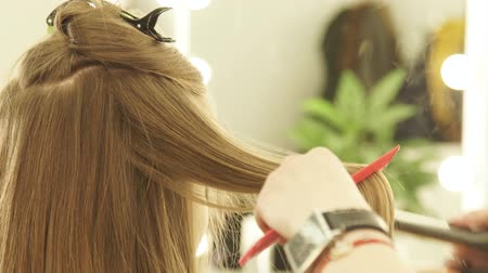 tongs : Female hairdresser using hair tongs and comb for hair straightening in beauty salon. Close up hairstylist straightening female hair during hairstyling in hairdressing salon.