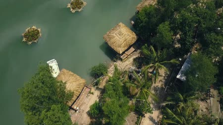 pier : Bungalows and boats among exotic palms and trees on river bank Aerial view. Tropical landscape with flying drones houses among tropical plants for recreation.
