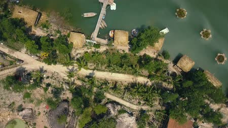 bungaló : Aerial shoot boat pier and bungalow for rest on lake among tropical nature on island. Green water in beautiful lake and palm trees drone view. Stock mozgókép