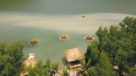 bungaló : Tropical bungalows with thatched roof and boat pier on shore green lake in resort hotel mountain aerial view. Cottages on shore mountain lake among exotic nature in water villa resort drone view. Stock mozgókép