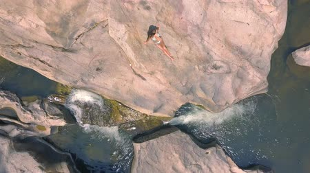 atirar : Beautiful woman in bikini sitting on big stone on river shore aerial view. Young woman resting and relaxing on large rock in river water drone shoot.