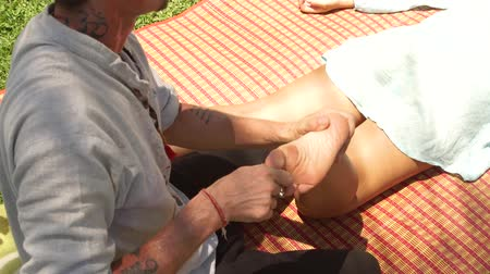 akupresura : Man doing thai foot massage to woman outdoor. Professional masseur doing yoga massage of female foot. Healthy and harmony lifestyle.
