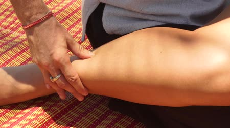 akupresura : Thai massagiste doing acupressure massage to woman leg outdoor. Close up traditional acupuncture body massage. Treatment and rehabilitation concept. Eastern medicine. Wideo