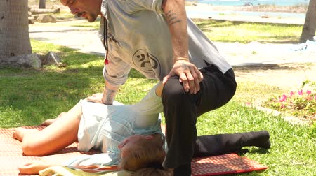akupresura : Body massage in yoga style. Thai massagiste doing stretching massage to woman outdoor. Traditional eastern medicine for treatment and rehabilitation body and spirit health.