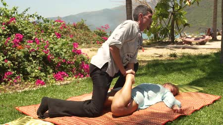 masażysta : Man massagiste doing stretching massage of female leg outdoor. Women getting thai body massage course. Healthy and harmony concept.