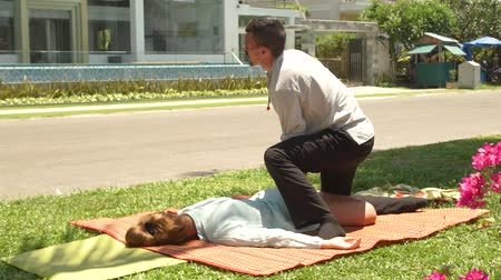akupresura : Yoga massagiste doing stretching massage of female leg outdoor. Professional thai massage for relaxation and recovery health. Treatment and healing concept. Wideo