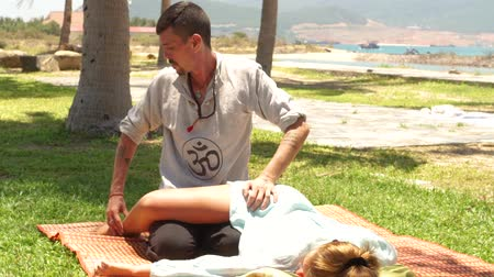akupresura : Thai massage outdoor. Massagiste doing acupressure massage to woman leg outdoor. Traditional acupuncture body massage. Healing and recovery body. Eastern medicine.