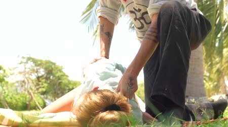 gyógyász : Woman receiving acupuncture massage. Massagiste doing yoga massage outdoor. Professional acupressure massage. Relaxation and rehabilitation concept.