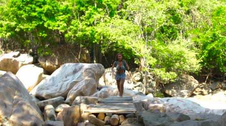 süspansiyon : Tourist woman walking on bridge over mountain river while summer hiking. Young woman walking on river bridge in tropical forest. Summer activities concept. Stok Video
