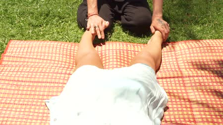 akupresura : Foot massage in yoga style outdoor. Thai massagiste making stretching foot massage to woman for relaxation and recovery outdoor. Thai and yoga massage in alternative and traditional medicine. Wideo