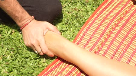 akupresura : Close up foot massage in thai style outdoor. Yoga massagiste doing stretching foot massage to woman for healing and recovery. Thai and yoga massage in traditional asian medicine.