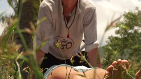 akupresura : Woman getting yoga massage from professional massagiste outdoor. Massagiste doing body massage in yoga style. Acupressure massage for body relaxation and recovery. Alternative and traditional asian medicine.