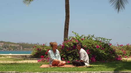 datas : Young man and woman talking in yoga lotus pose on sea beach. Man and woman sitting on turkish pose on green grass and talking on sea background.