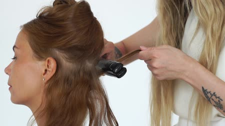anelzinho : Hairstylist curling hair with hair tongs while creating stylish hairstyle in beauty studio. Hairdresser using curling iron for stylish hairdo to longhaired woman. Stock Footage