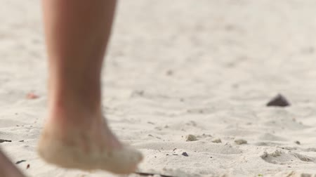 lépések : Wet female legs walking on sand close up. Barefoot woman walking on sand low view. Stock mozgókép