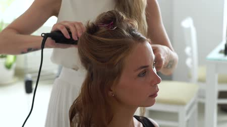 колечко : Hairdresser using hair tongs for curling while creating stylish hairstyle to young woman in beauty studio. Hairstylist making hairdo with hair iron to long haired woman.