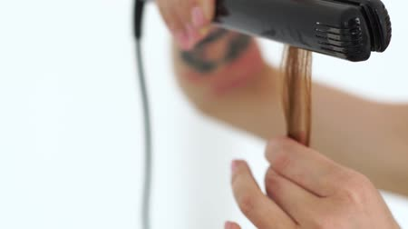 ringlet : Hairstylist using hair tongs for curling hair for stylish hairstyle in beauty studio. Close up hairdresser using curling iron for stylish hairdo to long haired woman. Stock Footage