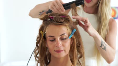 ringlet : Face young woman while curling using hair iron in beauty studio. Close up hairdresser making hairstyling with hair tongs to beautiful woman. Beauty and hairstyling concept Stock Footage
